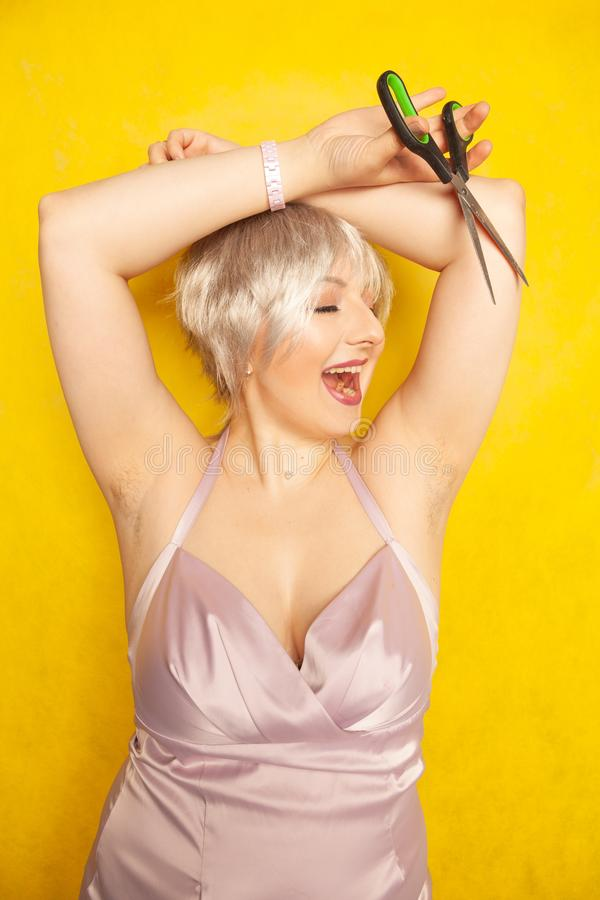 Mollig meisje in kleding met ongeschoren harige oksels en schaar ter beschikking op gele achtergrond in Studio royalty-vrije stock foto
