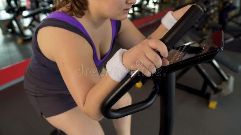 Mollig wijfje die hard aan stationaire fiets in sportclub, lichaamsgeschiktheid werken stock fotografie