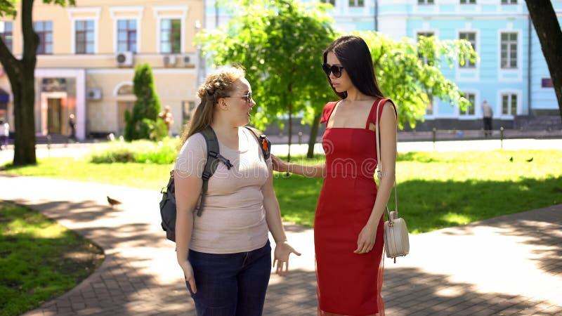 Mollige en slanke vrouwelijke vrienden die in park, lichaamscontrast, ondersteunende vriend debatteren stock foto's