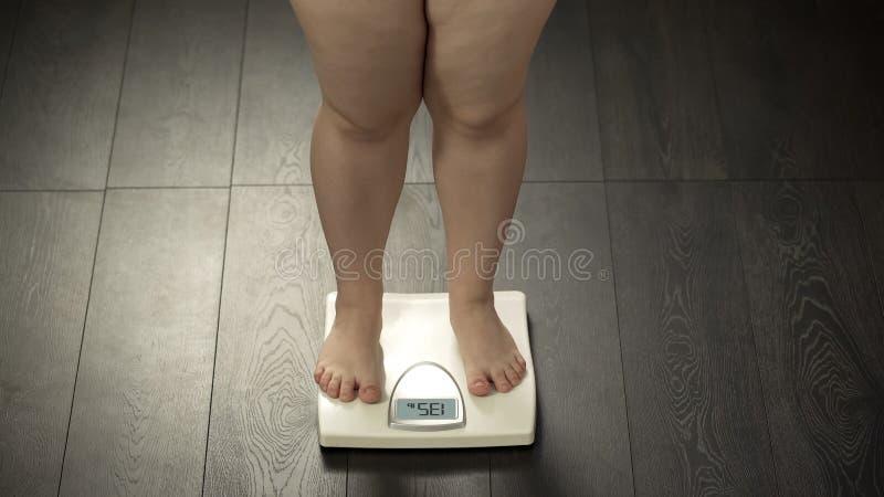 Mollige Frauenstellung auf Hauptskalen, Normalgewicht, erfolgreiches Diätergebnis stockfotos