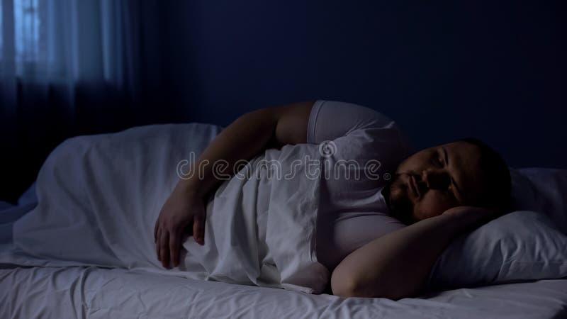 Mollige mensenslaap in bed, die bij nacht op comfortabele matras ontspannen, rust stock fotografie
