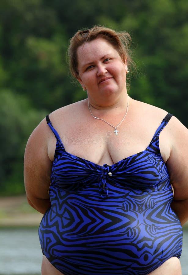 Mollige vrouw die zich dichtbij rivier bevindt stock fotografie