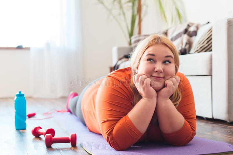 Molliger Frauensport zu Hause, der auf dem Mattenträumen glücklich liegt stockfoto