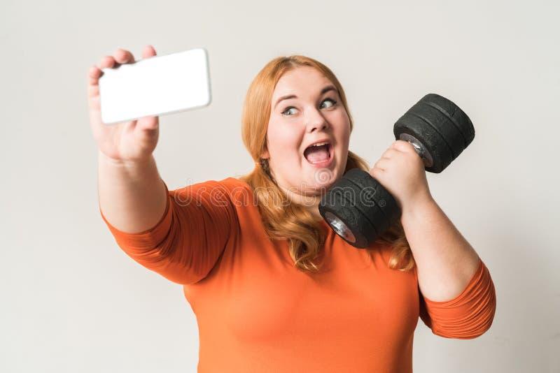 Molliger Frauensport zu Hause, der auf weißen nehmenden selfie Fotos mit dem Dummkopf aufgeregt lokalisiert steht stockfotos