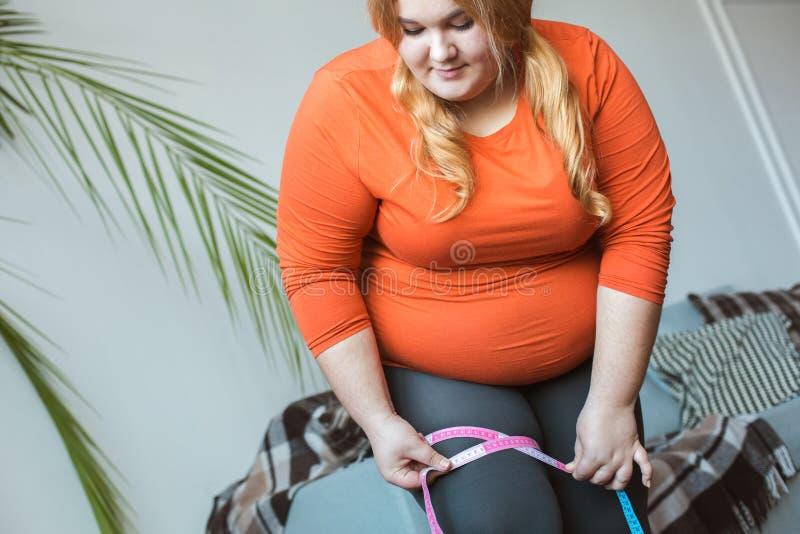 Molliger Frauensport zu Hause, der die messende Hüftengröße konzentriert steht stockbild