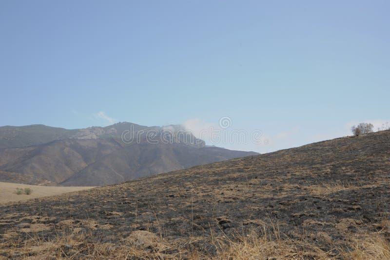 Moln över det brända berget royaltyfria bilder