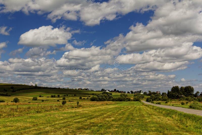 Moln över fältet på en solig dag arkivfoto
