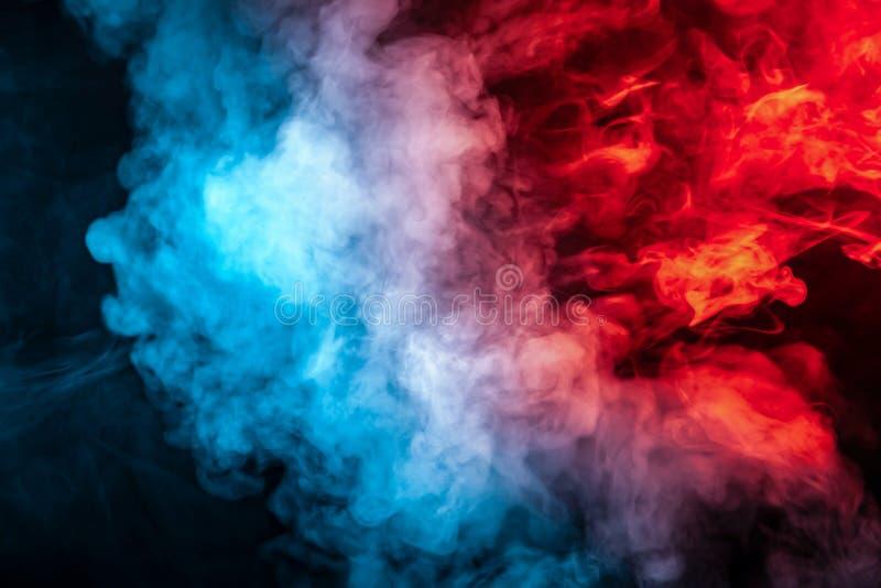 Moln av isolerad kulör rök: blått rött, apelsin som är rosa; bläddra på en svart bakgrund i mörkret fotografering för bildbyråer