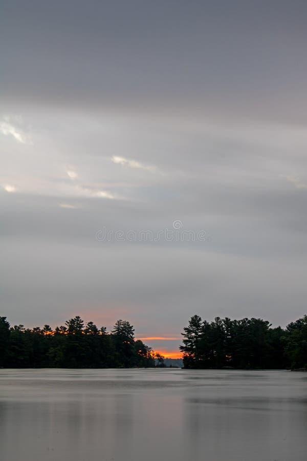 Moln dold soluppgångplats på Buckhorn sjön arkivbilder