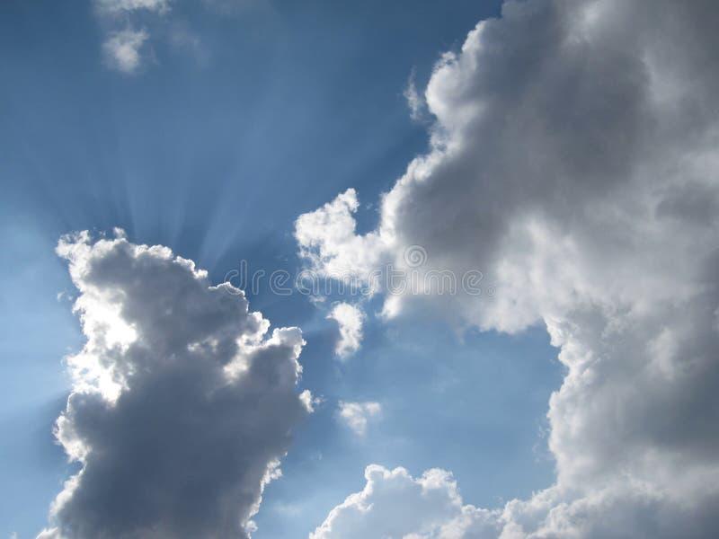 Moln för blå himmel och solstrålar arkivfoton