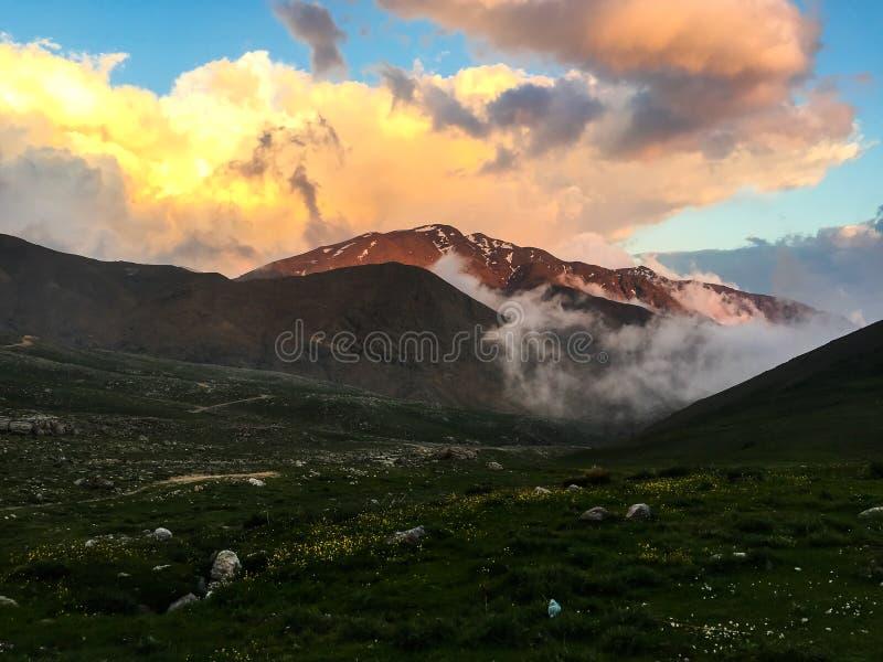 Moln i bergen på solnedgången arkivfoton