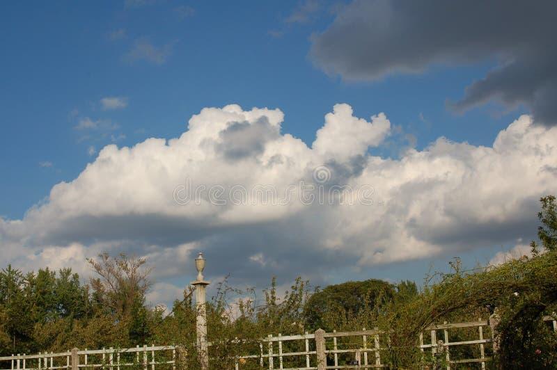 Moln i en blå himmel ovanför det vita staketet fotografering för bildbyråer