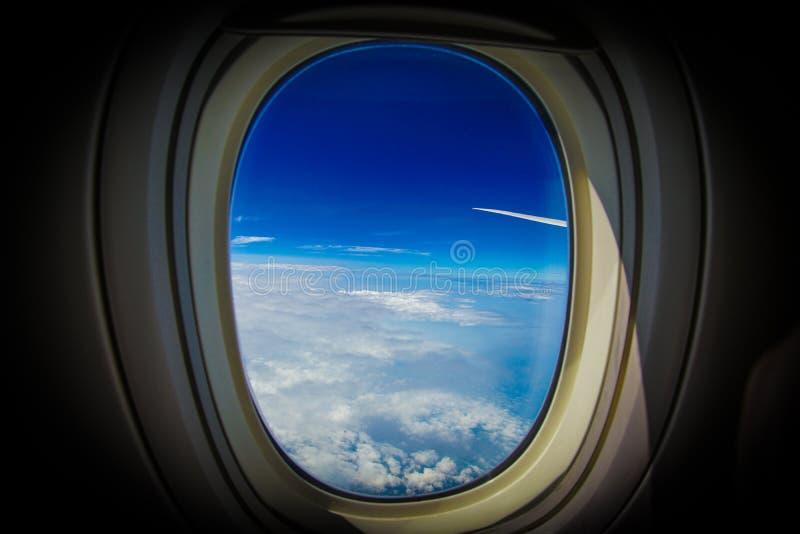 Moln och himmel som är synliga från fönstret av ett flygplan royaltyfria foton
