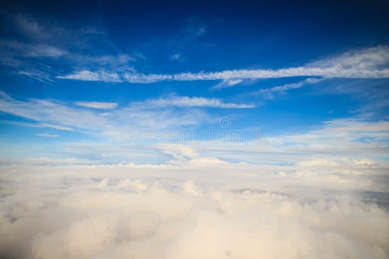 Moln och himmel som sett igenom fönster av ett flygplan Exotisk sikt från fönstret av ett flygplanflyg ovanför molnen Beautifu royaltyfri bild