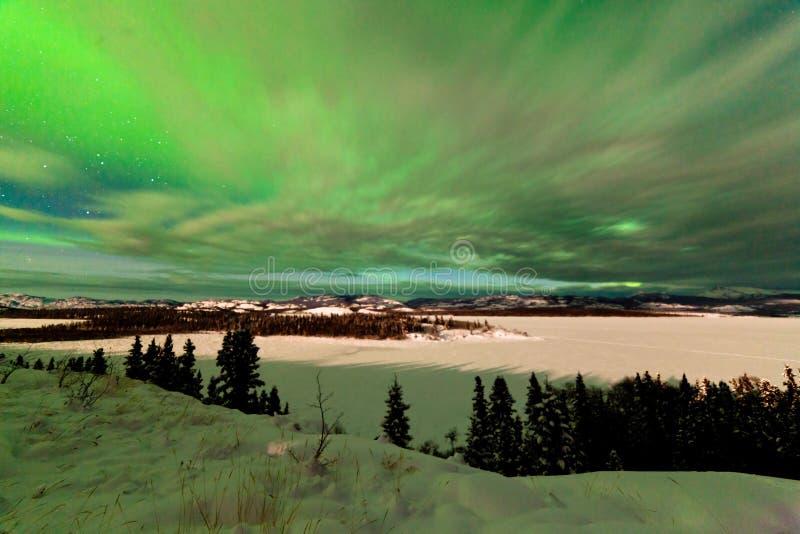 Moln och nordliga ljus över sjön Laberge Yukon arkivfoto