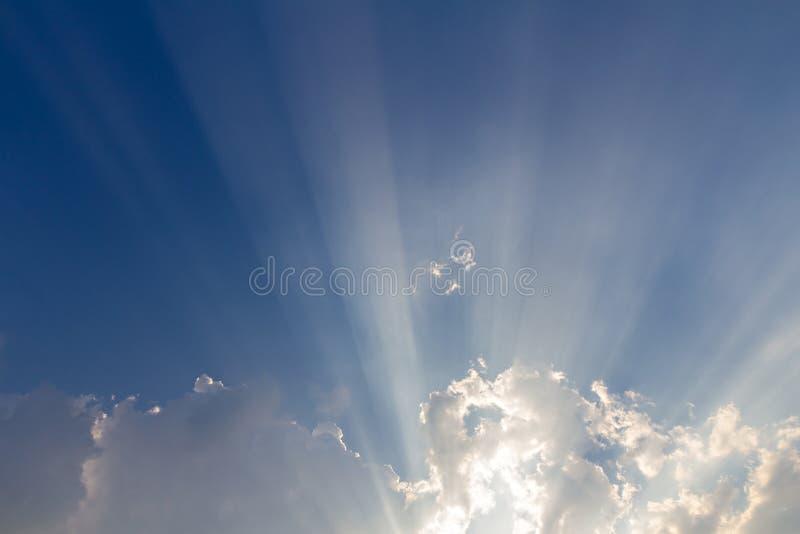 Moln och solstråle på blå himmel arkivfoton