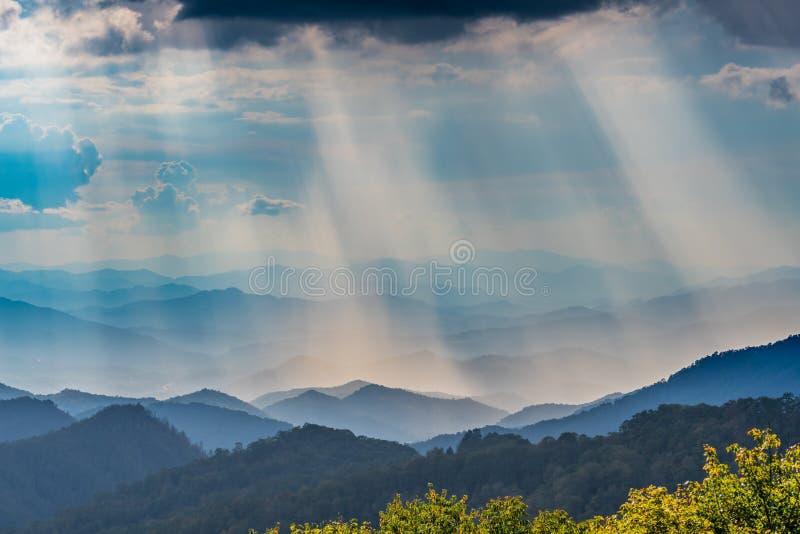 Moln ovanför solen Rays att skina på den blåa Ridge Mountains royaltyfri bild