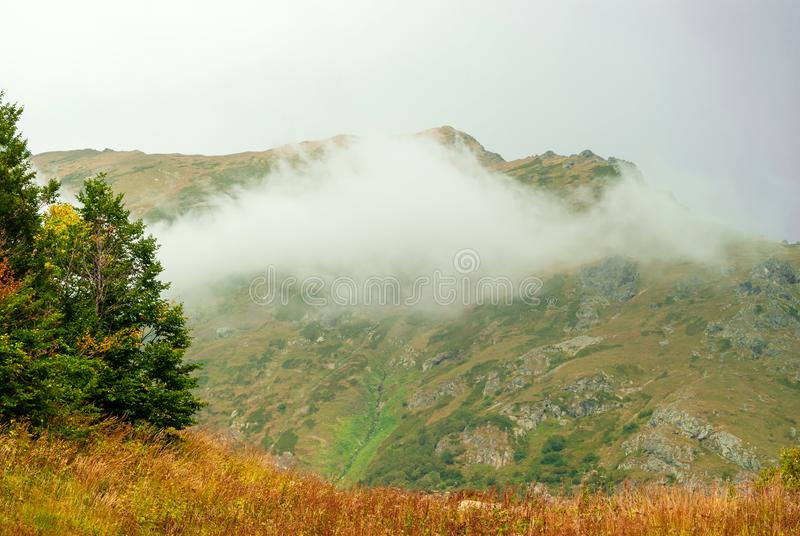 Moln på en bergssida arkivfoto