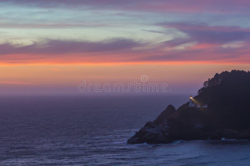 Moln reflekterar solnedgång över det Heceta huvudet arkivbild