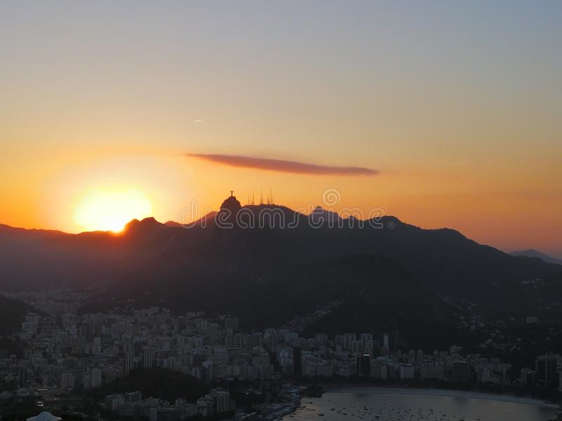 Moln, solnedgång, favela och Jesus royaltyfria bilder