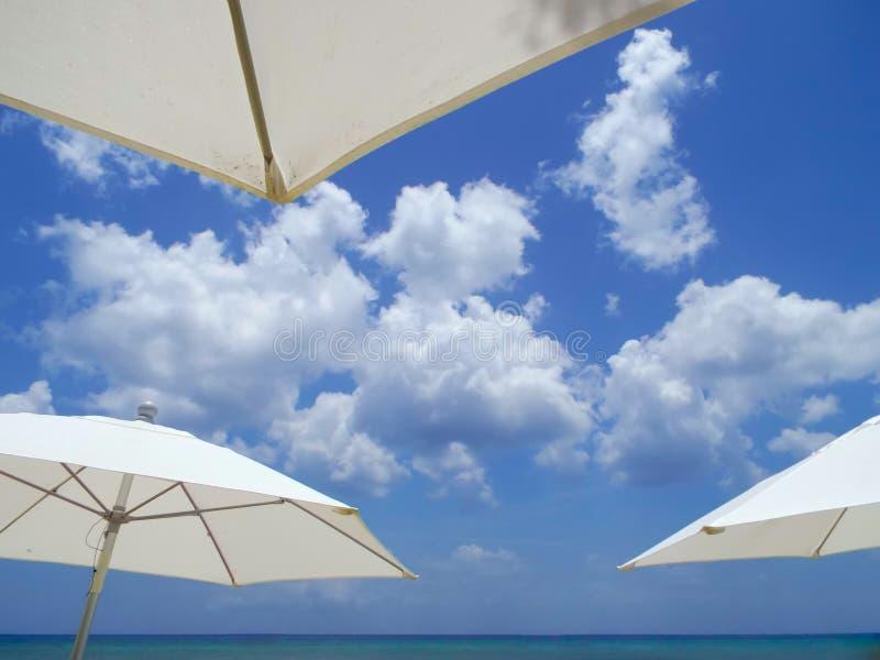 Moln som inramas av strandparaplyer royaltyfri fotografi