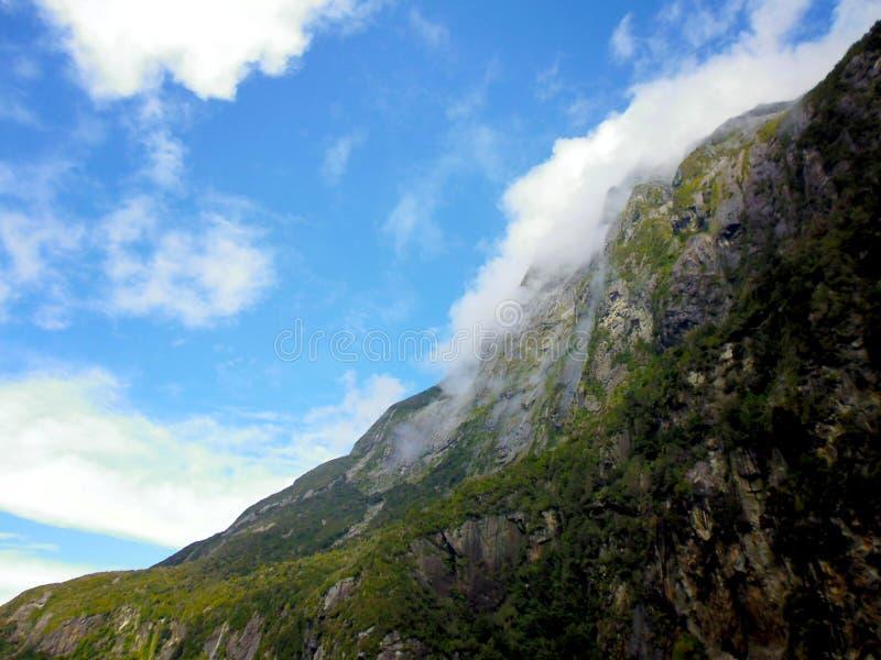 Moln som klättrar över fjordar på Milford Sound arkivbilder