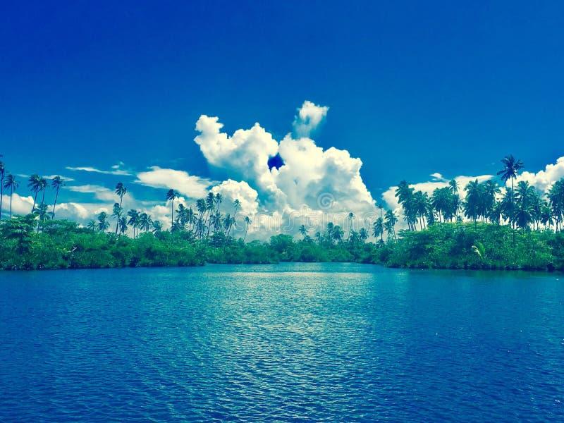 Moln som kysser i de blåa himlarna av Samoa royaltyfria foton
