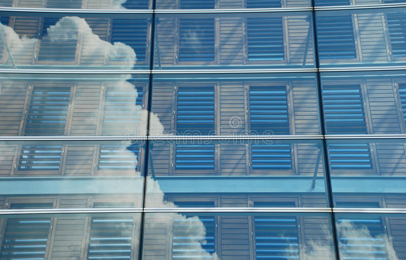 Moln som reflekterar i modern kontorsbyggnad royaltyfria bilder