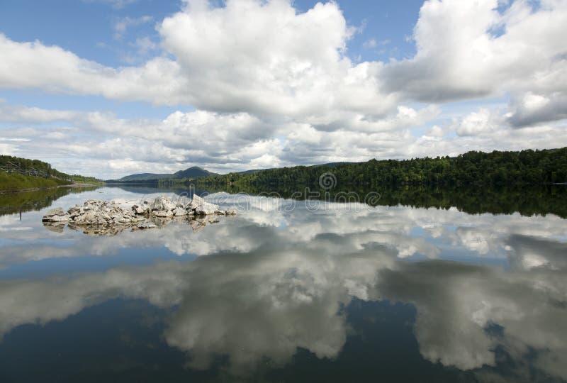 Moln som reflekterar på en sjö i Norge arkivbild