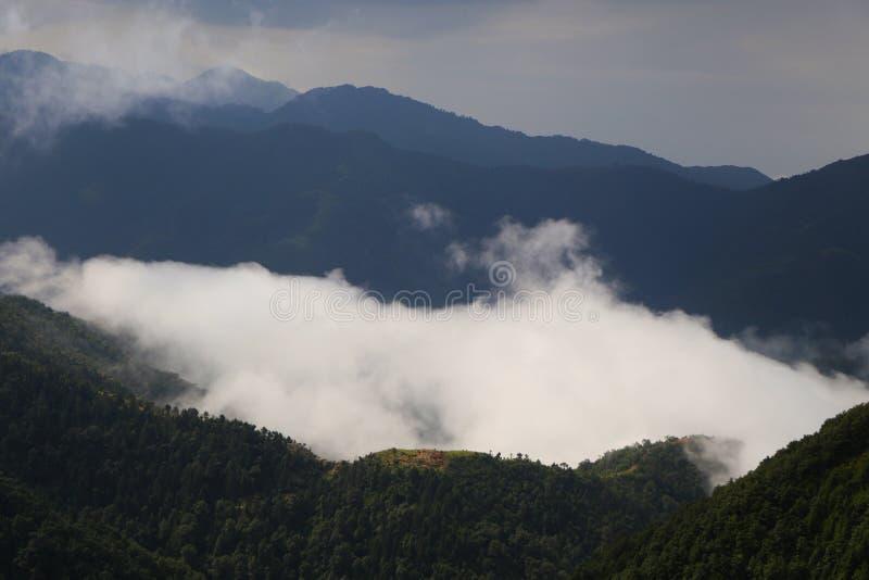 Moln som rullar mellan kullar av himachal arkivbilder