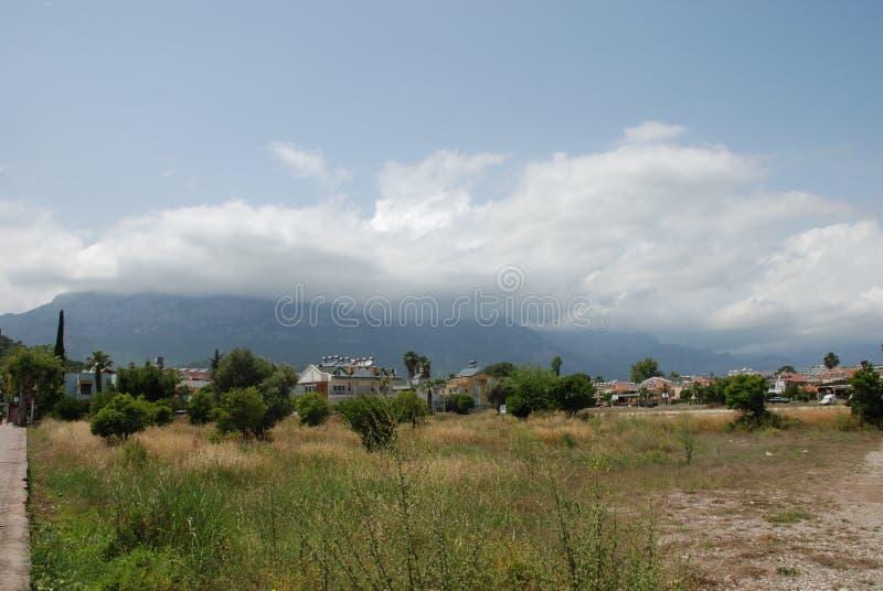 Moln stiger ned nedanför bergmaxima ovanför bergstaden arkivbild