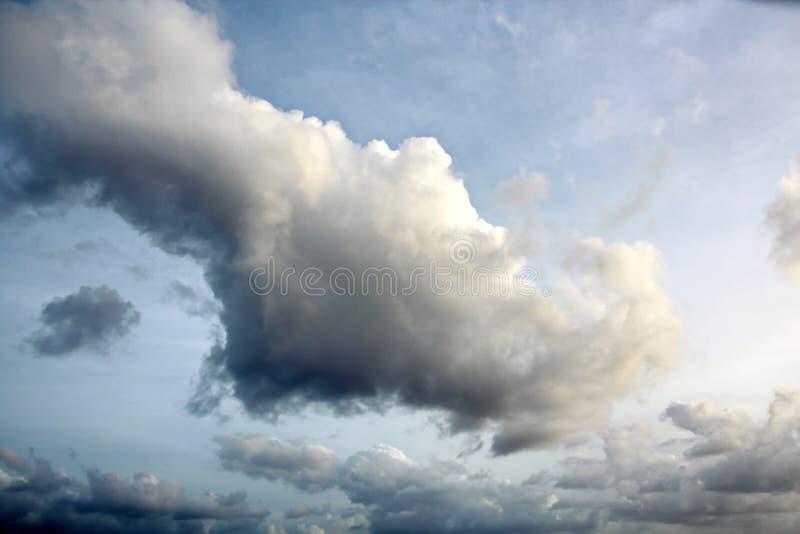 Molnen är mångfärgade dånande bisarra former mot den blåa himlen och solen ovanför havyttersidan royaltyfri foto