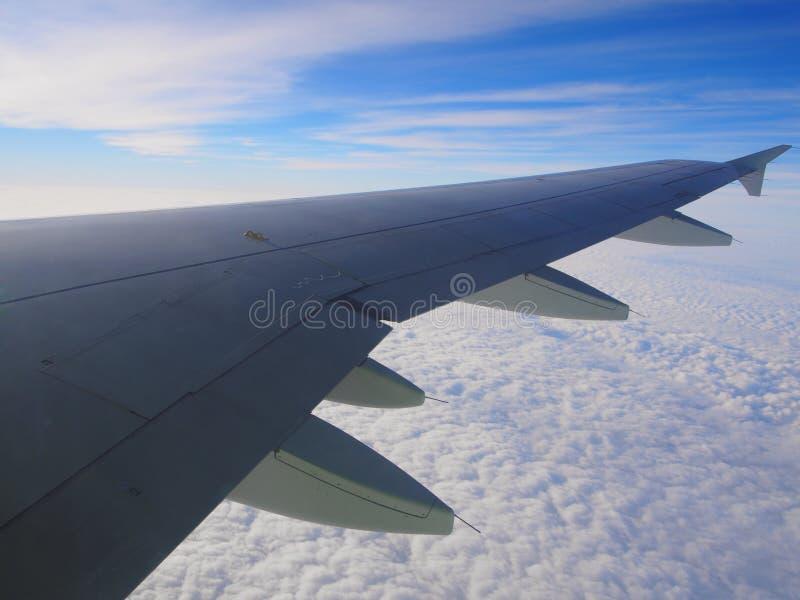 Molnen, himmel och vingen arkivbild
