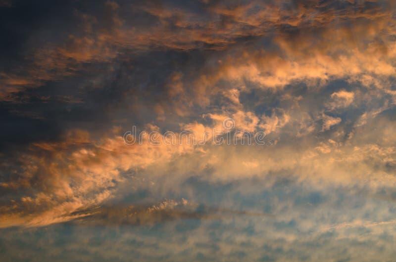 Molnen i aftonhimlen är upplysta vid ljuset av solen som går utöver horisonten arkivfoto