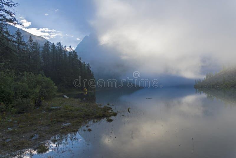 Molnen ligger på yttersidan av en bergsjö royaltyfri foto