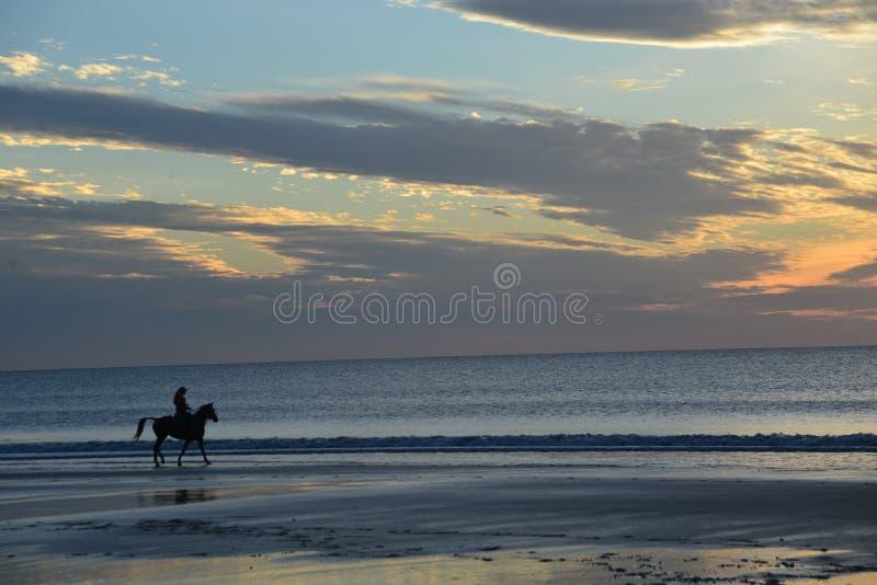 Molnen välkomnar strandsoluppgången och besökarna som går och rider arkivbilder