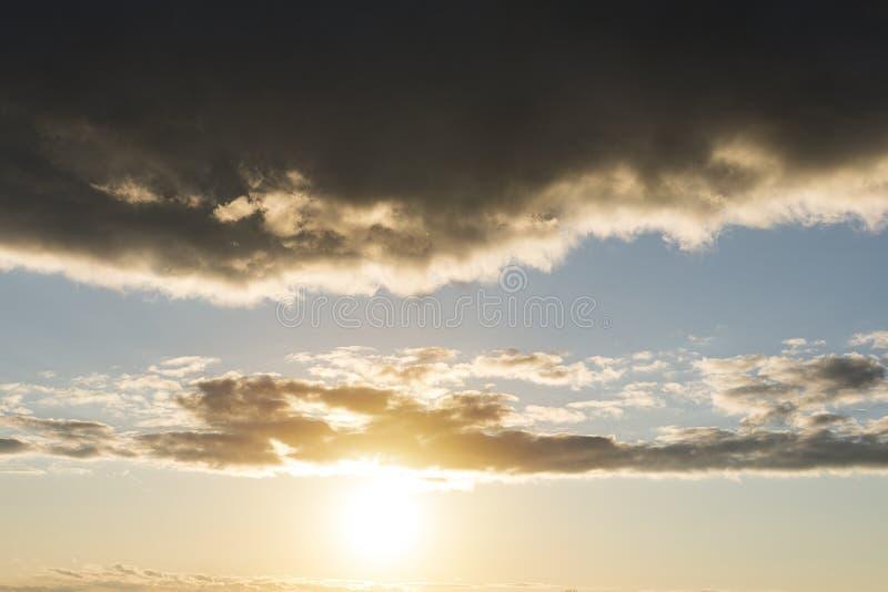 Molnet med härligt solljus och guld- himmelbakgrund, härlig solljusbortgång till och med ett stort svart regnmoln Solnedgång in arkivfoton