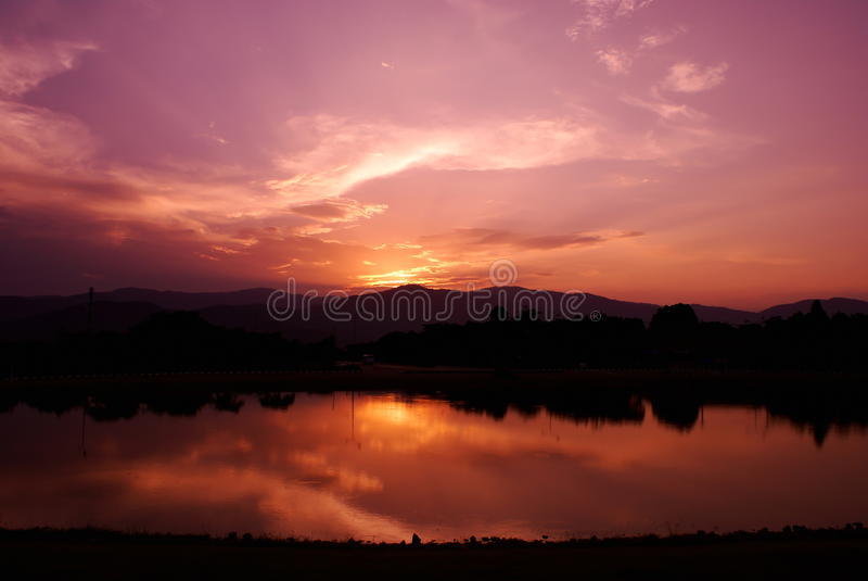 Molnhimmel och solstråle med sjön royaltyfri bild
