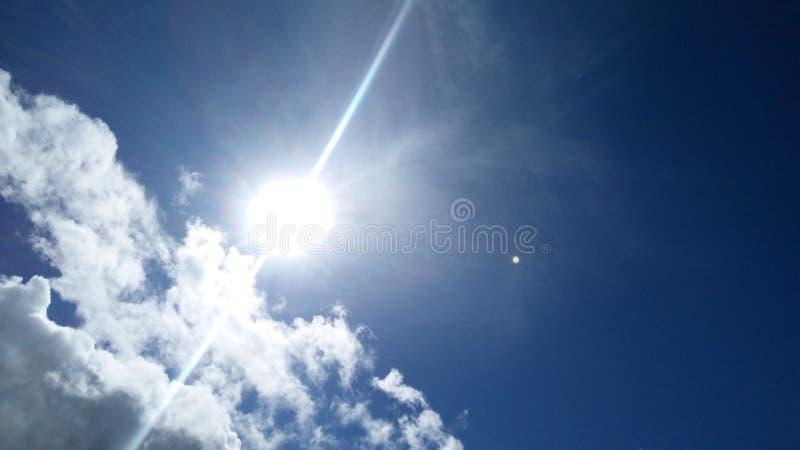 Molnig blå himmel med The Sun ljus arkivfoto