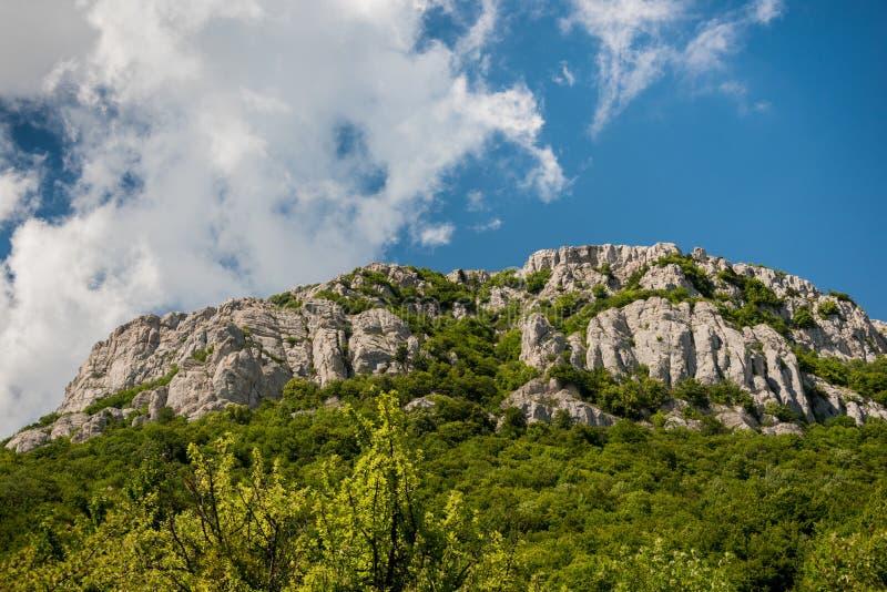 Molnig himmel över grön bergskedja arkivfoton