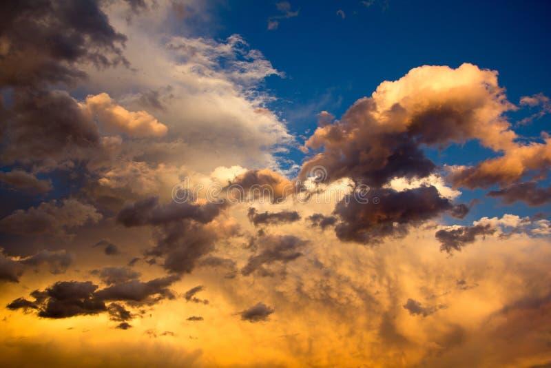 Molnig himmel för grå färger och för guling under solnedgång royaltyfri fotografi