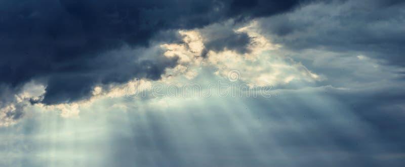 Molnig himmel för härlig mörk storm med strålar av solen som bryter till och med moln fotografering för bildbyråer