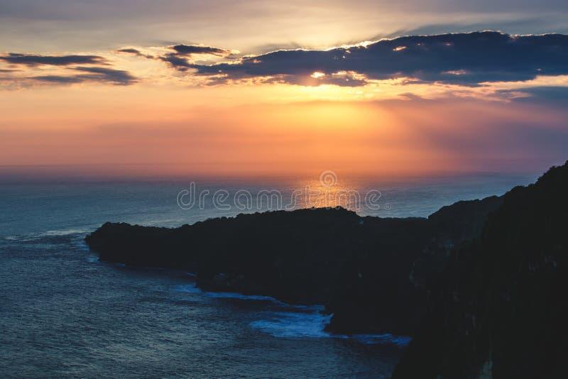Molnig himmel för solnedgång över havet och klippan, Bali arkivbilder