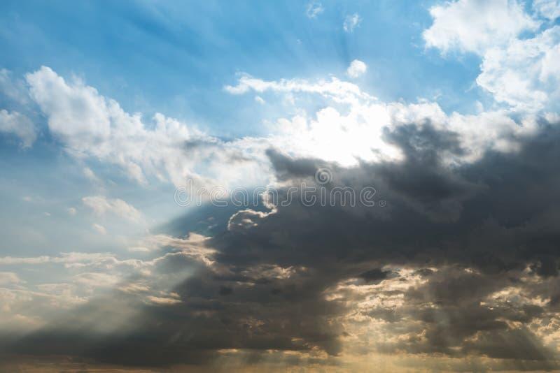 Molnig himmel och blått gör klar himmelmoln och sunburst- eller solstrålen på royaltyfri fotografi