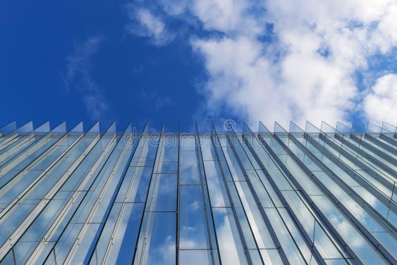 Molnig himmel reflekterade i glasväggen av en modern byggnad fotografering för bildbyråer