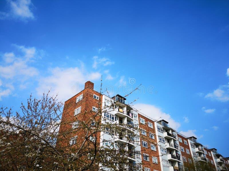 Molnig klar himmel med tappningbyggnad arkivbild
