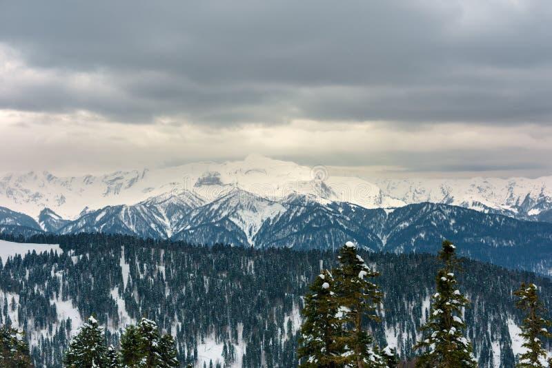molnig liggande Snö-korkade berg och låga moln royaltyfri fotografi