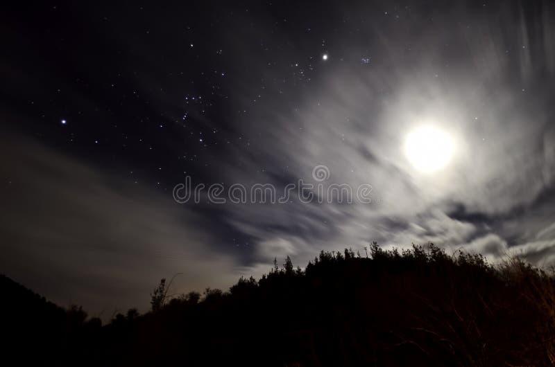 Molnig natt med stjärnor och månen royaltyfri bild