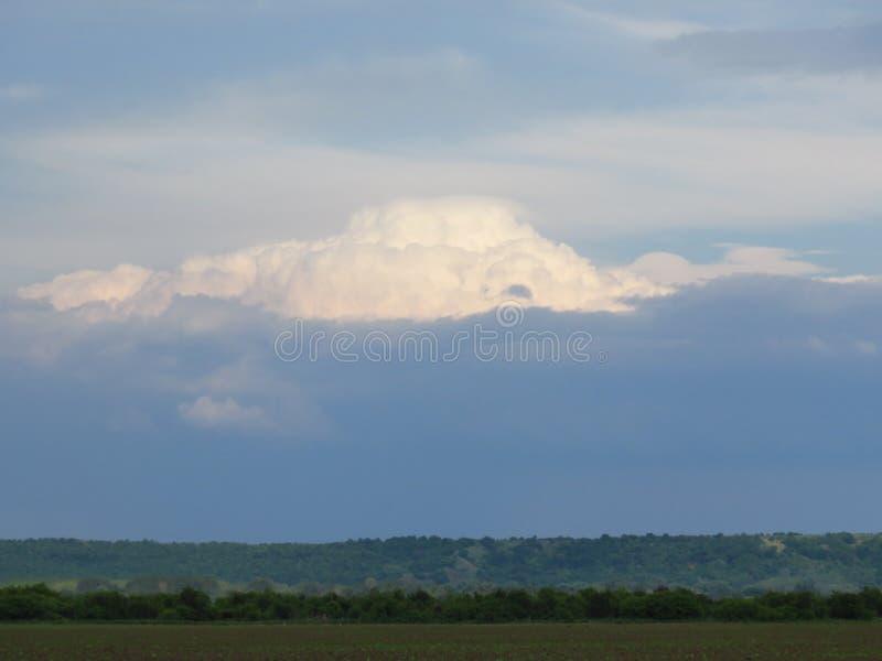 Molnig solnedgång över en grön kulle Vitt pösigt moln i den blåa himlen arkivfoton