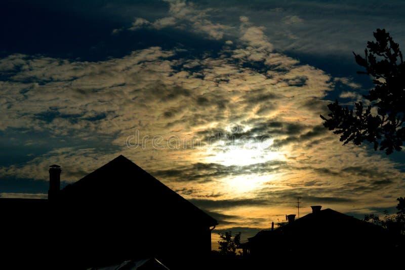Molnig solnedgång i by royaltyfria foton